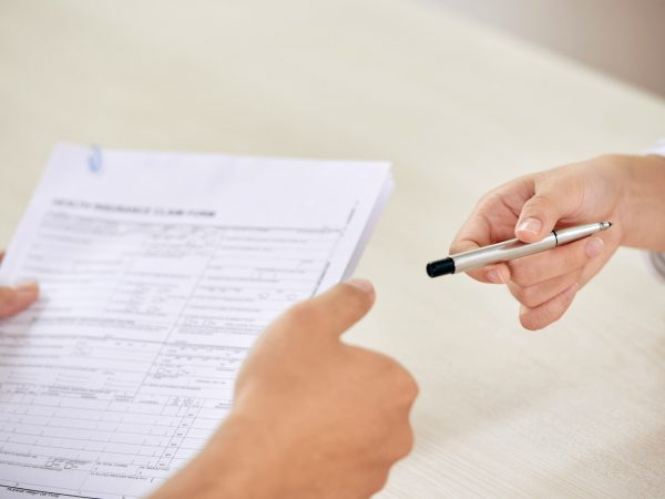Crop person giving pen to colleague for signing paper contract on business meeting
